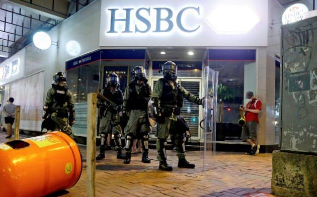 デモに備えて機動隊員が警備している香港・湾仔地区にあるHSBCの支店前。同行の経営には前例のない困難が待ち受けている=ロイター