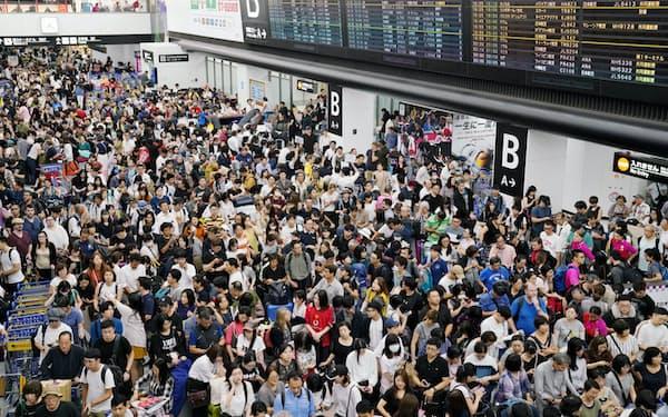足止めされた利用客で混雑する成田空港の到着ロビー(9月9日)