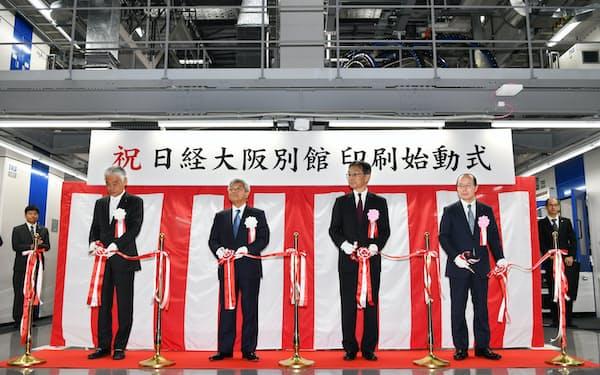新工場の始動式でテープカットする日本経済新聞社の岡田社長(左から2人目)ら=9日、大阪市城東区