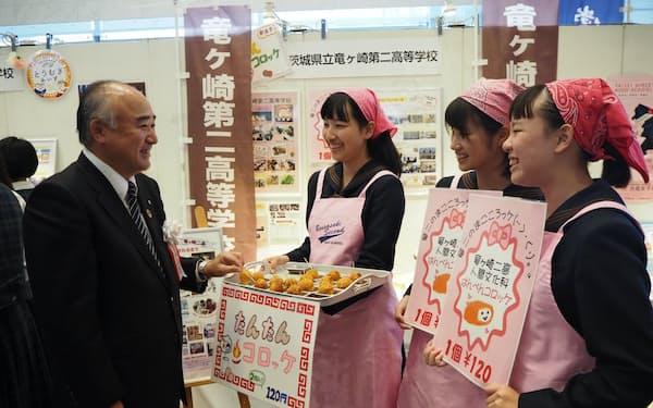 出展した高校生と話す筑波銀行の生田雅彦頭取(左)(9日、茨城県つくば市)