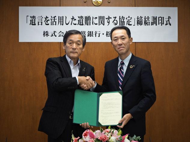 締結書に調印した千葉県松戸市の本郷谷健次市長(左)と千葉銀行の篠崎忠義取締役