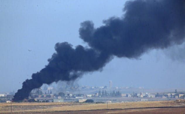 シリア北東部ではトルコ軍の爆撃を受けて炎上する場面がみられた(9日)=AP