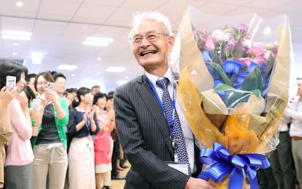 旭化成の社員から贈られた花束を手にする吉野彰名誉フェロー(10日、東京都千代田区)