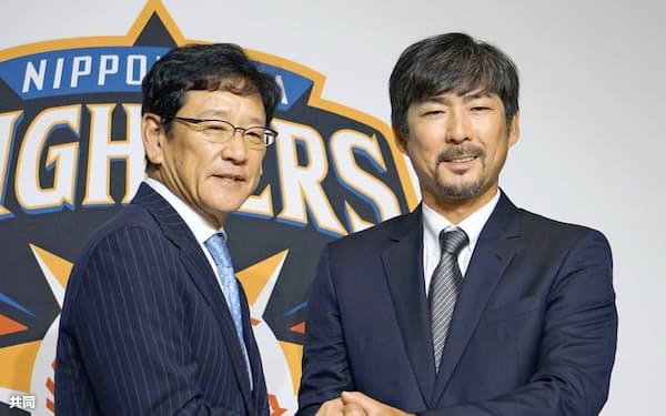 日本ハムの栗山英樹監督と笑顔で握手する、小笠原道大新ヘッド兼打撃コーチ(10日、札幌市内のホテル)=共同