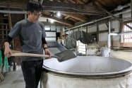 蒸し米の工程で使う「甑」。現在はスコップで蒸したコメをすくっている(8日、石川県小松市)