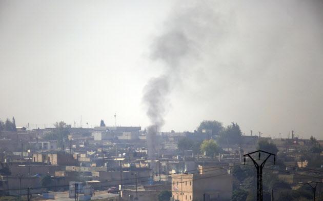 シリア北東部ラス・アルアインで、トルコ軍の砲撃の間に上がった煙(10日、トルコ側から撮影)=AP
