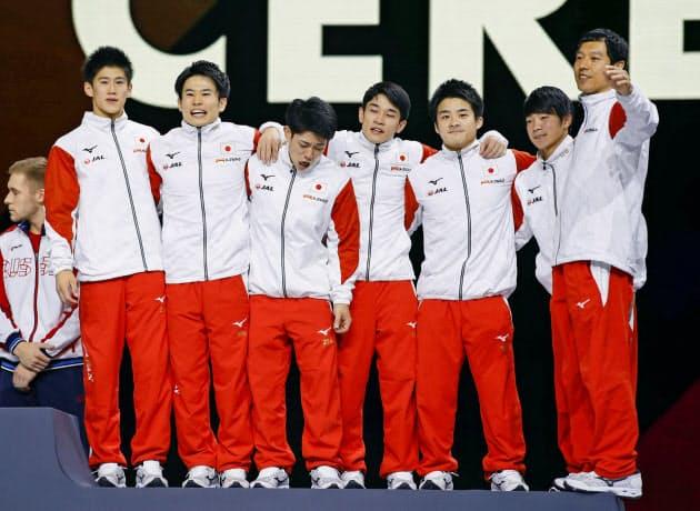 男子団体総合で3位となり、表彰台に上がる日本チーム=共同