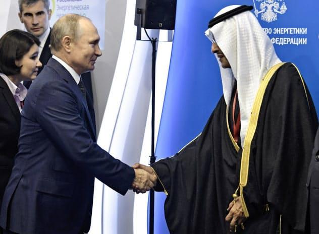 2日、モスクワを訪問したサウジアラビアのアブドルアジズ・エネルギー相と握手するプーチン大統領=AP