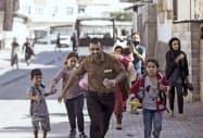 10日、シリア側からの砲撃から逃げ惑う人々(トルコ南部アクチャカレ)=AP