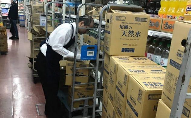 台風を前に水などが品薄になり、従業員は補充に追われている(都内のスーパー)