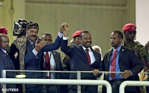 18年7月、エリトリア大統領の手を取るエチオピアのアビー・アハメド首相(中央)=ロイター