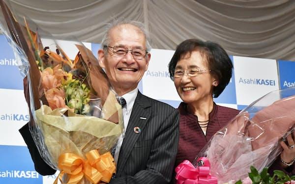 記者会見で花束を手に笑顔を見せる旭化成の吉野彰名誉フェロー(左)と妻の久美子さん(10日、東京都千代田区)