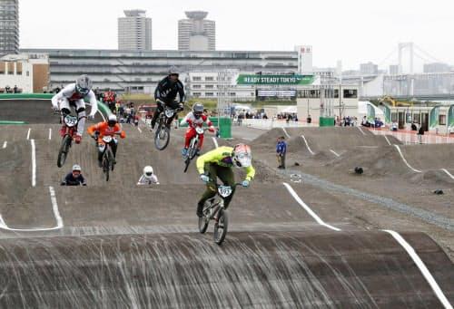 本番会場となる有明アーバンスポーツパークで行われた、自転車BMXレースの東京五輪テスト大会。右奥はレインボーブリッジ(11日、東京都江東区)=共同