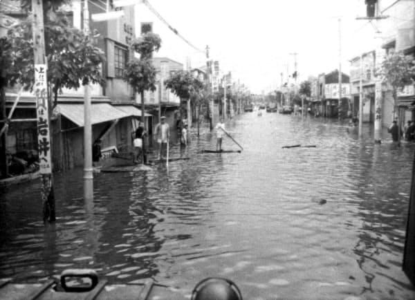 狩野川台風の影響で浸水した町中をいかだで渡る人たち(1958年9月27日、東京・葛飾)=共同