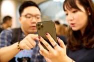 アップルの新型スマホを手に取る中国の消費者(2019年9月、北京)=ロイター