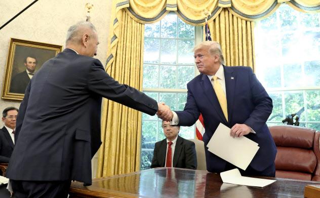 ホワイトハウスで握手するトランプ米大統領と劉鶴・中国副首相(11日、ワシントン)=AP