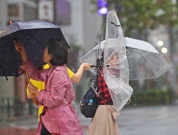 強風のなかを歩く人たち(12日午後、東京都新宿区)