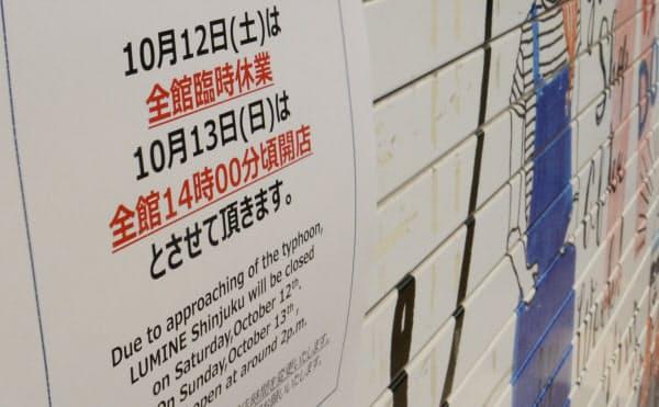 台風19号の影響で臨時休業を伝える商業施設の張り紙。13日午後に営業を再開する小売りが多い(12日、東京都新宿区)
