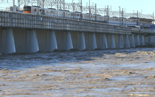 計画運休が解除され、増水した多摩川の上を通る電車(13日午前、東京都世田谷区)