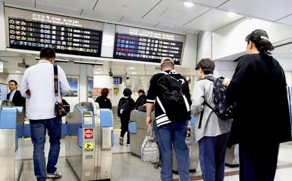 東海道新幹線がおおむね時刻通りの運行開始となり、早朝から改札を通る人たち(13日午前5時50分、JR東京駅)=共同