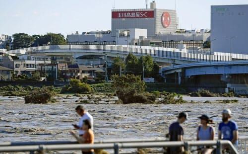 台風19号による大雨で増水し濁流となった多摩川。東京都世田谷区では氾濫した(13日午前7時48分)=共同