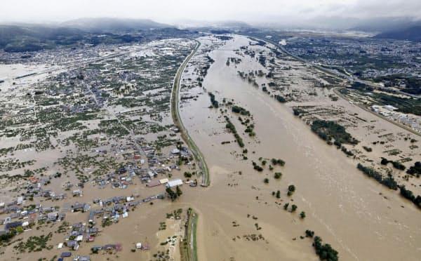 台風19号による大雨で増水し氾濫した千曲川。中央左は決壊した堤防(13日午前8時15分、長野市穂保)=共同