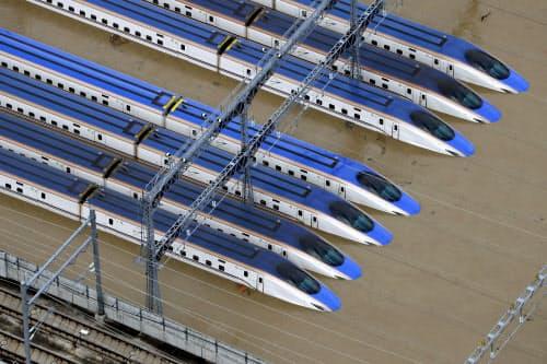 台風19号による大雨で水に漬かった車両基地に並ぶ新幹線(13日午前8時6分、長野市赤沼)=共同