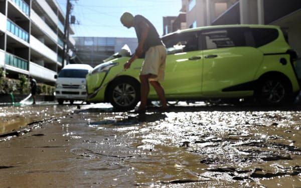 台風19号から一夜明け、住民たちは汚泥の掃除に追われた(13日午前、東京都世田谷区)