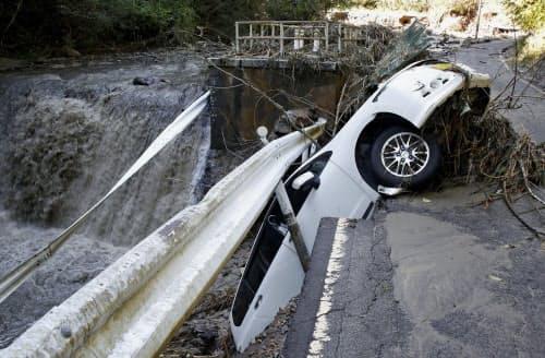 台風19号の大雨による影響で陥没した道路の路肩に落ちた乗用車(13日午前、宮城県角田市)=共同