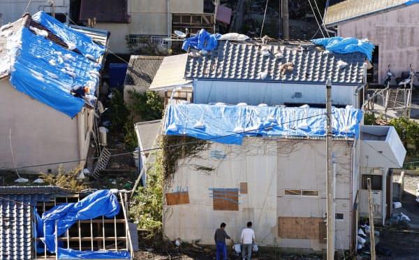 台風19号の暴風雨で剥がれ落ちた屋根のブルーシート。先の台風15号で受けたとみられる被害が今も残る(13日午前、千葉県鋸南町)=共同