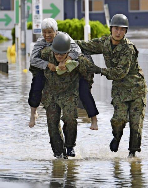 阿武隈川が氾濫した福島県本宮市で自衛隊員に救出される高齢者(13日)=共同