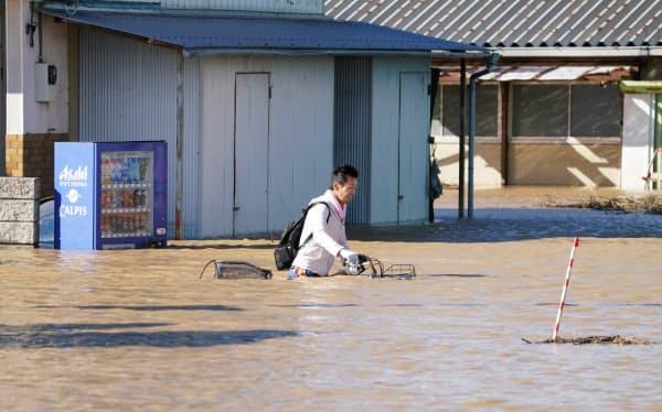浸水した道路を自転車を押して歩く人(13日、埼玉県川越市)=樋口慧撮影