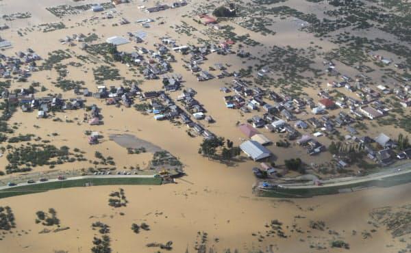 堤防が決壊し氾濫した千曲川(下)と広範囲に冠水した長野市内(13日)=小高顕撮影