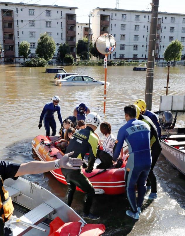 台風19号の大雨で浸水した埼玉県坂戸市の住宅街で行われる救助活動=13日午後2時15分(共同)