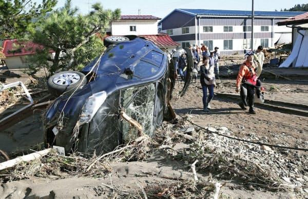 氾濫した川の水に流され大破した車(13日、宮城県丸森町)=共同