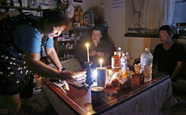 停電の中、ろうそくやライトの明かりで夜に備える家族。佐久間恭子さん(68)(左)は「避難所だと気を使って眠れないだろうから、ここに居ることにしました。電気と水道が早く復旧してほしいです」と話した(13日、宮城県丸森町)=共同