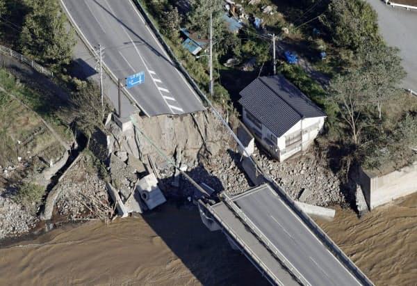 千曲川に架かる橋の近くの道路が陥没した現場(13日、長野県東御市)=共同
