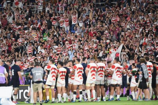 試合終了後、健闘をたたえ合う両チームの選手に拍手を送るスタンドの観客