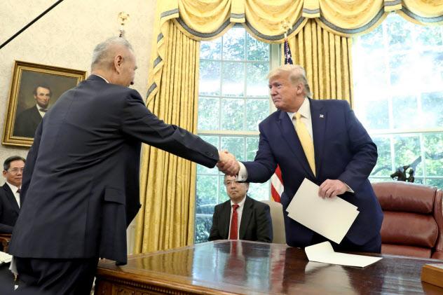 11日、劉氏(左)との会談で中国が米農産品を大量に買うことで合意したと主張していた=AP