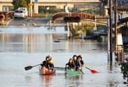 台風19号による大雨で千曲川が決壊し、ボートで救助される人たち(13日午後4時45分、長野市豊野町豊野)=共同