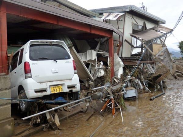 濁流に流されたとみられる車が住宅に突っ込んでいた(14日、長野市)=村越康二撮影