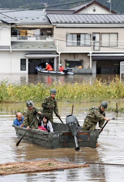浸水した住宅地から自衛隊員に救助される住民(14日、宮城県丸森町)=共同