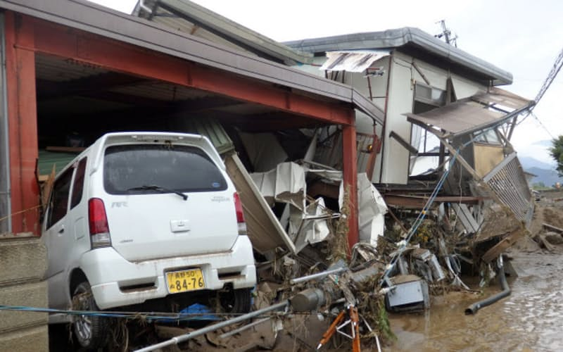 濁流に流されたとみられる車が民家に突っ込んでいた(14日、長野市)