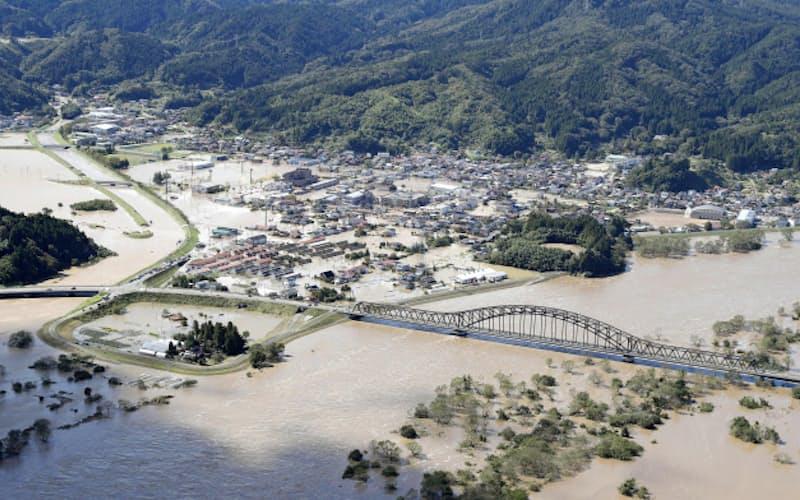 台風19号の影響で阿武隈川(手前)が氾濫し、浸水した宮城県丸森町の市街地(13日午前)