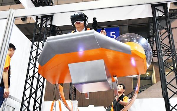 VRゴーグルを装着し「空飛ぶクルマ」の乗車体験ができるタイコエレクトロニクスジャパンのブース(14日、千葉市美浜区の幕張メッセ)
