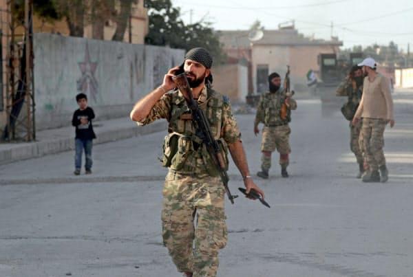 シリア北部テルアビヤドを歩くトルコ軍側のシリア反体制派兵士(13日)=ロイター