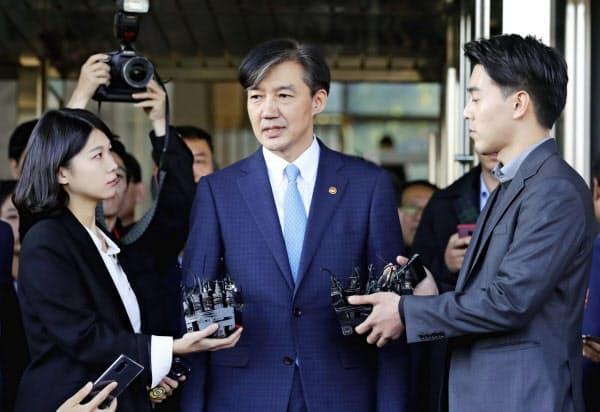 辞任を表明した後、記者団に囲まれる曺国法相(14日、ソウル)=聯合・共同