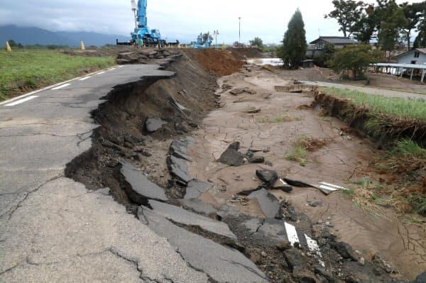 崩れ落ちた道路。奥は決壊した堤防で進む復旧作業(15日午前、長野市)