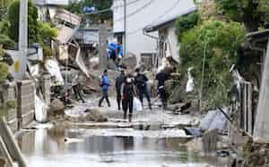 浸水被害を受けた住宅街の様子を見に戻る人たち(15日午前、長野市)
