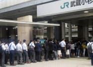 構内が浸水した川崎市のJR武蔵小杉駅で入場が規制され、列に並ぶ利用客ら(15日午前)=共同